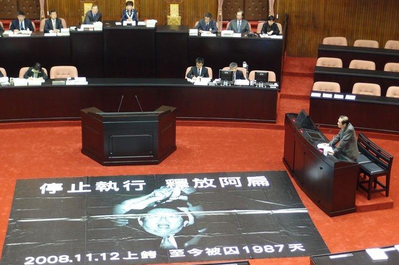 2014年5月9日第八屆第五會期總質詢,陳唐山在議場內鋪上陳水扁上銬布幕引發社會極大震撼。(前衛出版社提供)
