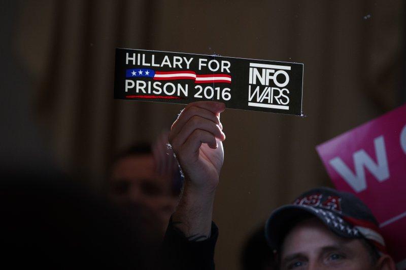 川普支持者舉的「送希拉蕊進牢房」的標語。(美聯社)