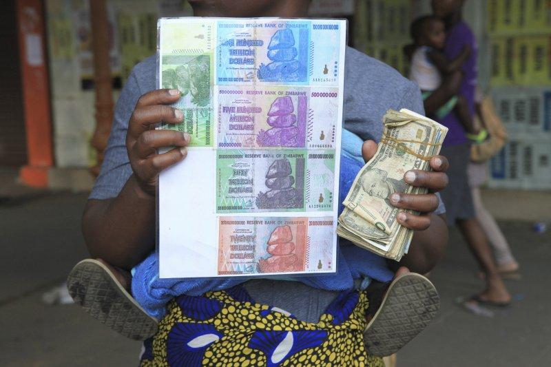 一位匯兌黃牛在街頭拿著一疊美鈔,還有一張舊辛巴威元的護貝圖例招攬收購舊鈔。(美聯社)