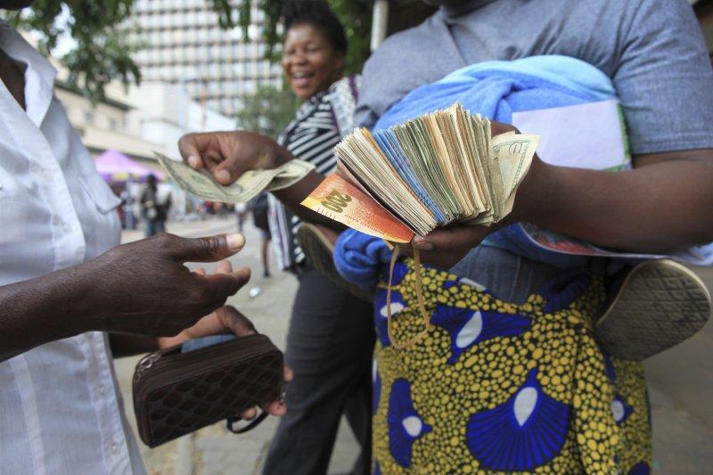 一位匯兌黃牛在街頭收購舊鈔,一張面額100兆的辛巴威他願意花5美元收購。(美聯社)