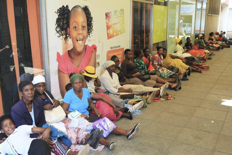 辛巴威民眾在銀行外排起長隊,等待領款。(美聯社)