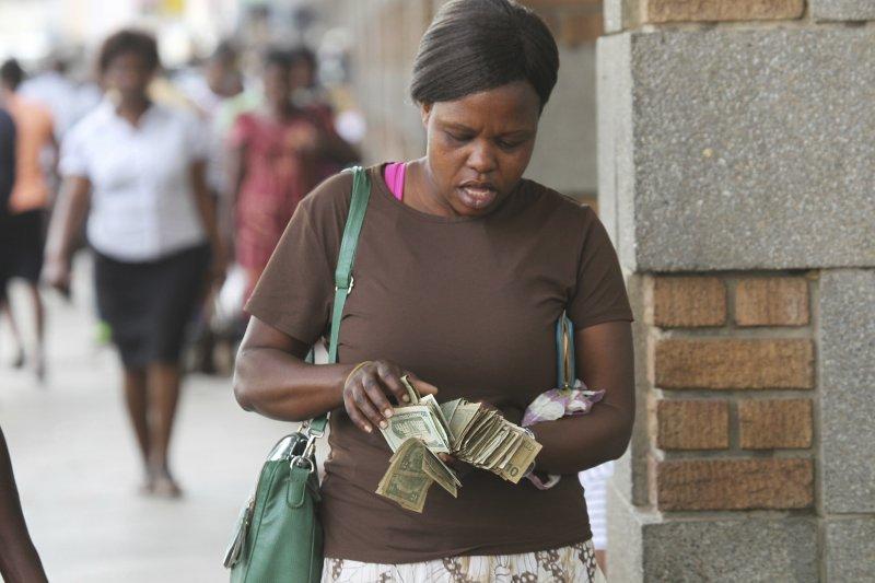 一位匯兌黃牛在街頭清點美鈔。(美聯社)