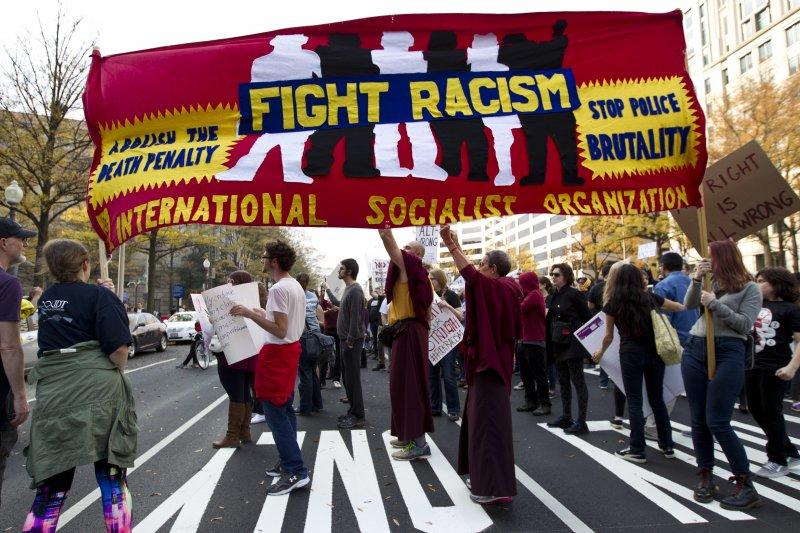 美首府華盛頓抗議川普的民眾,高舉「對抗種族主義」的旗幟。(美聯社)