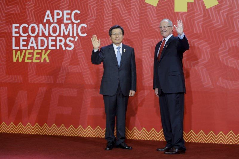 代替南韓總統朴槿惠出席APEC峰會的黃教安(左),預計在返抵南韓後會立即在《獨立檢察法案》上簽字。右邊為祕魯總統庫琴斯基(美聯社)