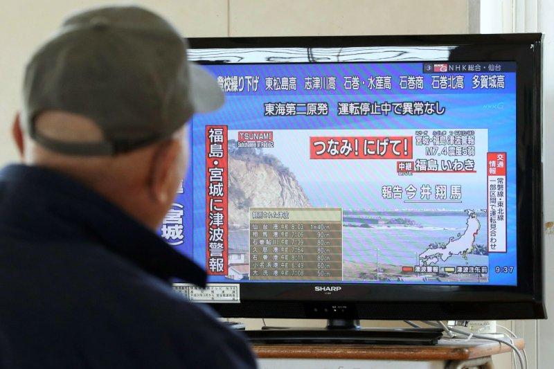 一位日本老人正在收看海嘯警報。(美聯社)