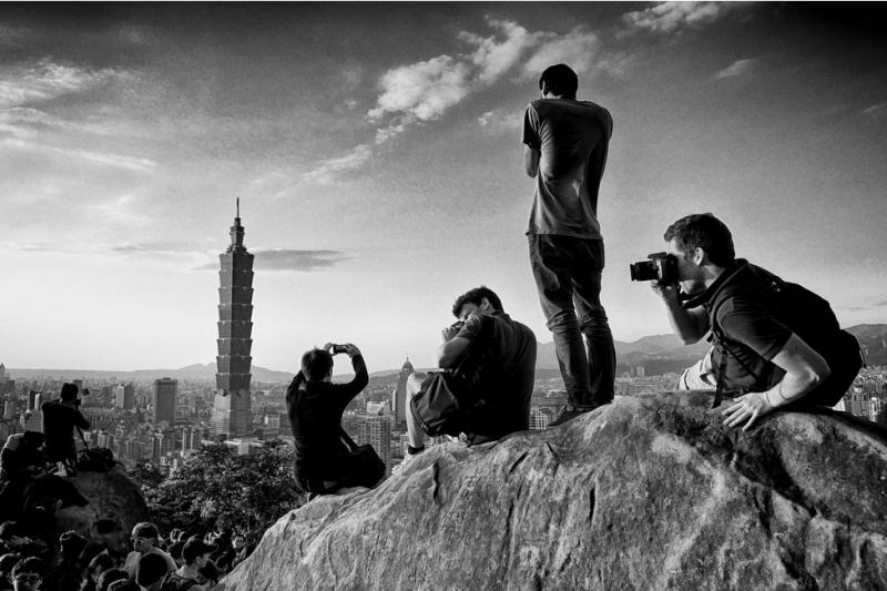 狄樂平的照片作品《獵影》獲得照片組冠軍,他以旁觀者角度拍攝象山上正在取景的國外遊客,成功呈現出象山正成為眺望台北盆地最佳的景點之一。(取自台北悠遊行網站)
