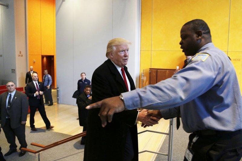 總統當選人川普與紐時的記者及編輯會面,並與紐時總部的保全握手。(美聯社)