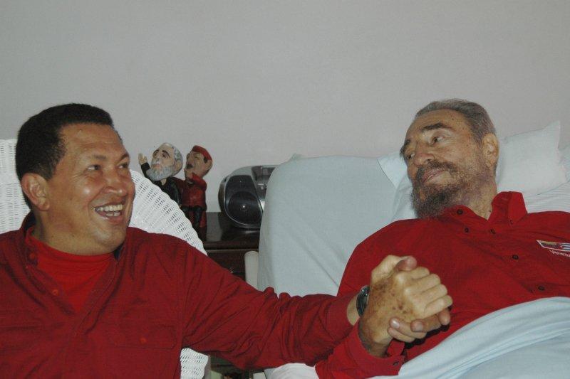2006年,手術後靜養的菲德爾・卡斯楚(右)拉著前來探望的委內瑞拉時任總統查維茲(Hugo Chavez)的手(AP)