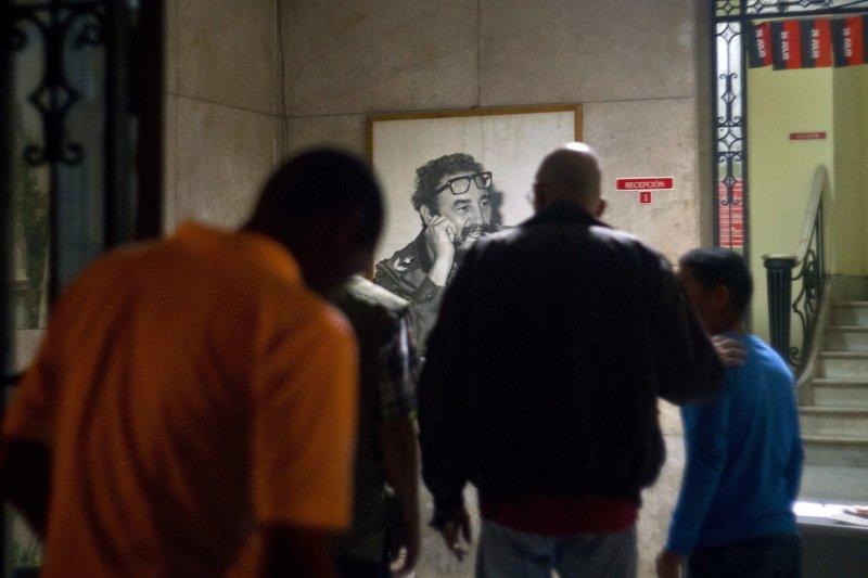 古巴民眾群聚在老卡斯楚的照片前哀悼,為他逝世的消息難過不已。(美聯社)