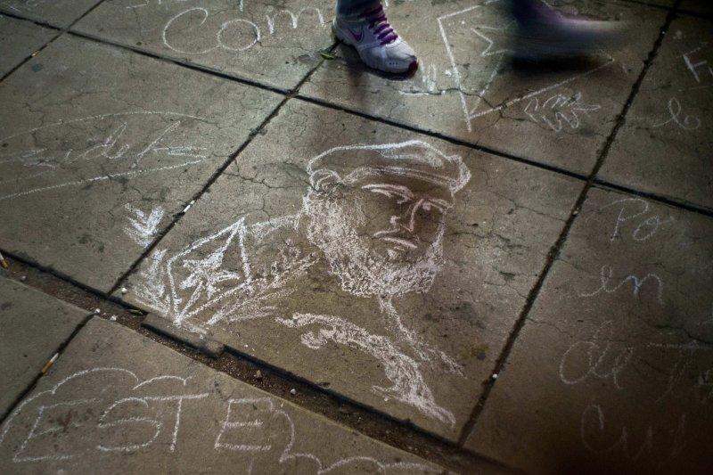 古巴民眾在地板上畫上老卡斯楚的畫像,以表思念。(美聯社)