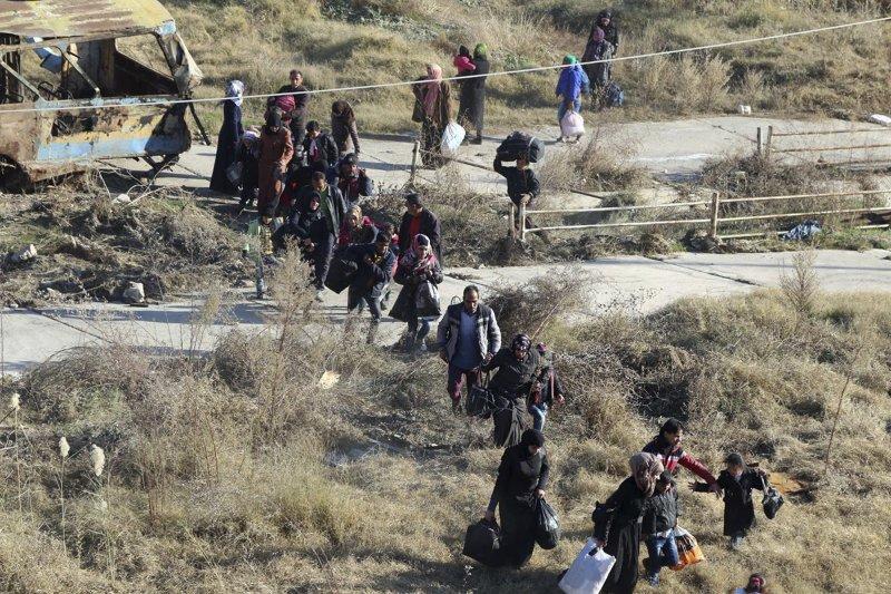 阿勒坡東北部的民眾湧入庫德族士兵佔領的謝赫法瑞斯區。(美聯社)