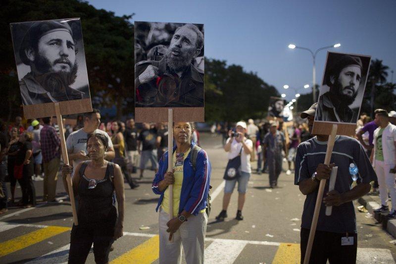 追悼卡斯楚過世的古巴民眾,在哈瓦那街頭舉著他們心目中偉大領導人的肖像。(美聯社)