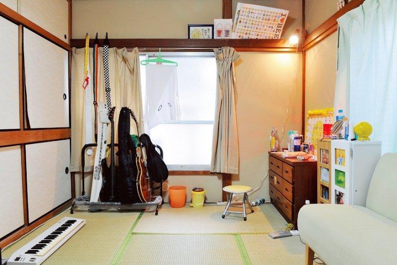 空蕩的房間整齊地疊著一把把樂器,出於對音樂的狂熱而即使過著較為刻苦地生活,依舊甘之如飴。(圖/時報出版提供)