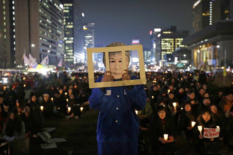 南韓民眾在首爾街頭抗議,要求總統朴槿惠立刻下台。還有人戴上她的面具,暗示總統應該下獄。(美聯社)