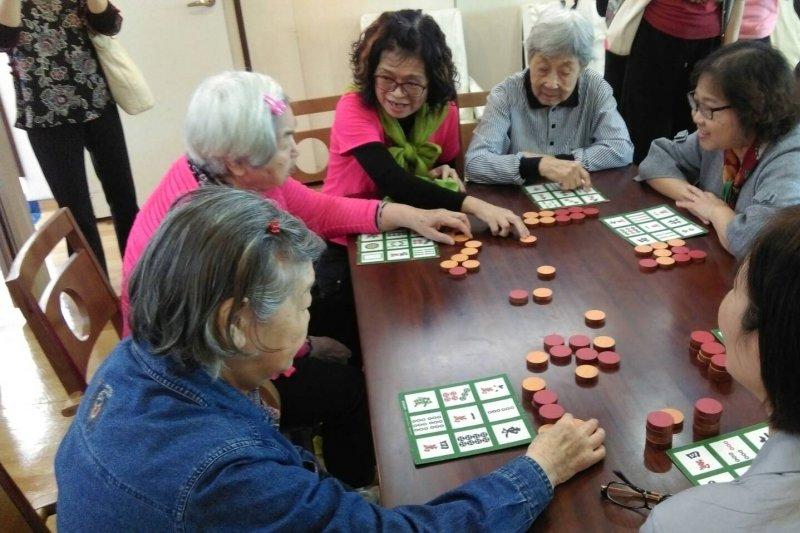 西湖日間照顧中心中長者互動交流,大玩起麻將賓果。(黃麒珈攝)