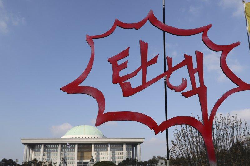 南韓國會9日就朴槿惠總統彈劾案進行表決,民眾在國會大廈前樹立韓文「彈劾」標語。(AP)
