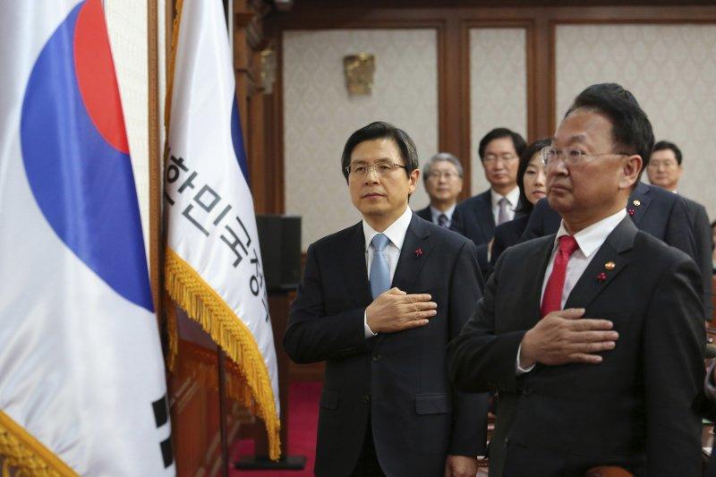 在南韓總統朴槿惠確定遭彈劾後,國務總理黃教安(左)在內閣會議前向國旗敬禮。(美聯社)