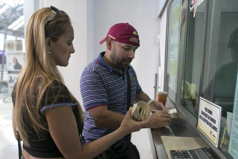 委內瑞拉民眾拿著大疊的玻利瓦紙鈔,在鄰國哥倫比亞邊境城市的商場裡換成哥倫比亞披索,準備購買民生用品(AP)