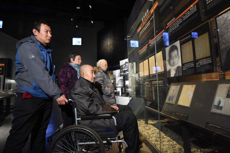 12月13日,在侵華日軍第七三一部隊罪證陳列館,78歲的侵華日軍第七三一部隊受害者遺屬原文慶看著殉難的父親原美臻的照片在輪椅上沉默良久。(新華社)