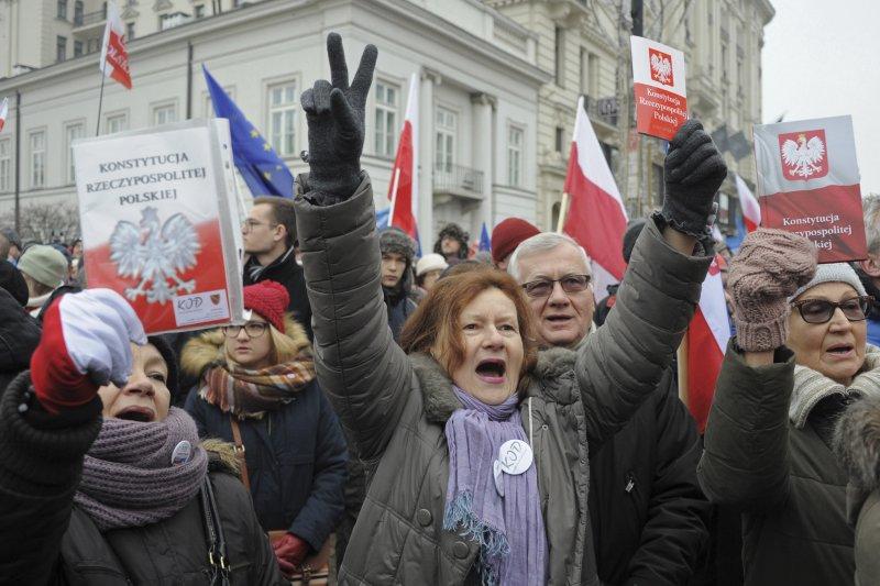 波蘭執政黨PiS自行通過預算案疑似違憲,示威群眾秀出波蘭憲法抗議(AP)