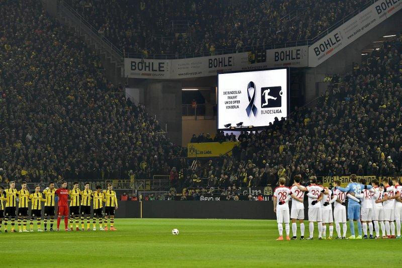 20日的德甲賽事舉行前,兩隊球員與全場球迷對柏林卡車恐攻的死難者默哀。(美聯社)