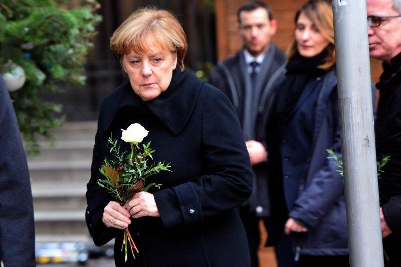 德國總理梅克爾20日在柏林卡車恐攻的事發地獻花致哀。(美聯社)