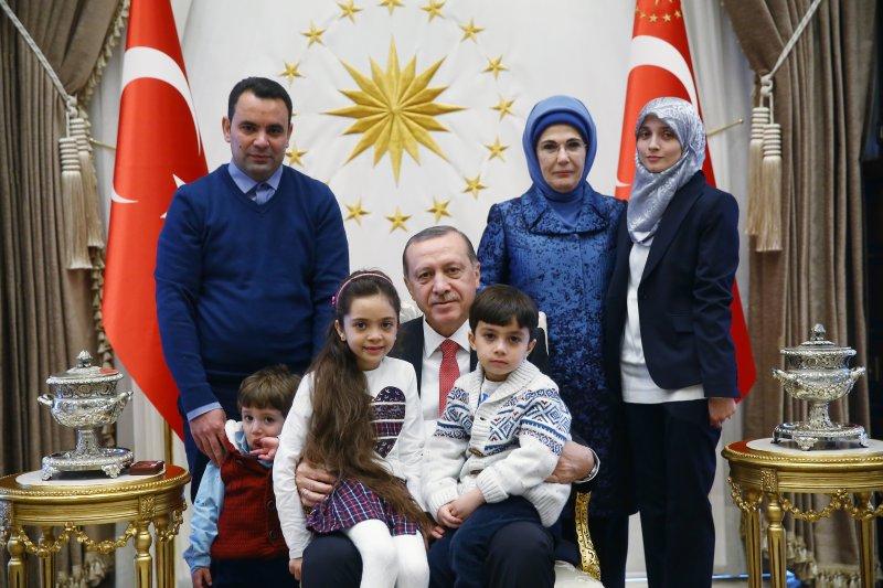 芭娜(左前)、芭娜的弟弟(右前)被土耳其總統艾爾多安(中)抱在懷裡,芭娜的母親法蒂瑪(右)與父親迦山(左)也一起入鏡。(AP)
