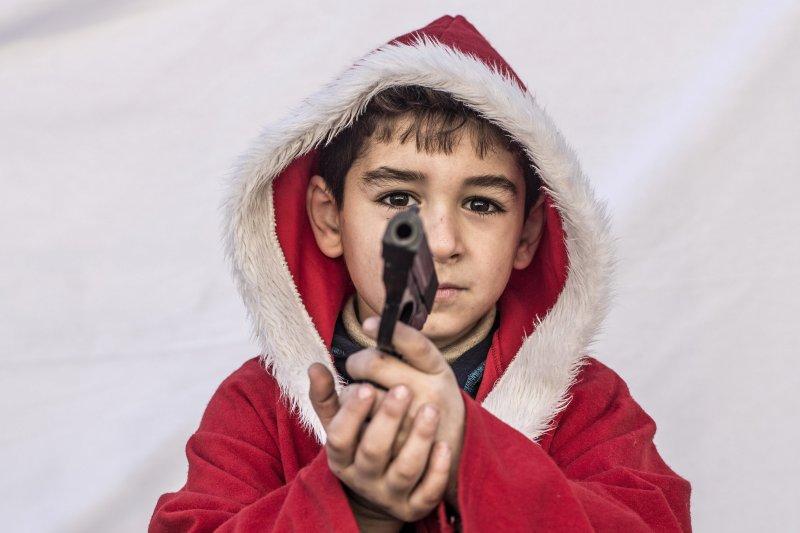 伊斯蘭教國家伊拉克的基督徒們,今年依舊過著顛沛流離的生活,更別說要好好和家人過一個聖誕節,住在難民營裡的凱亞克斯(Kayaks)今年才7歲,穿著一身紅的聖誕老人裝,手上卻舉著玩具槍。(AP)