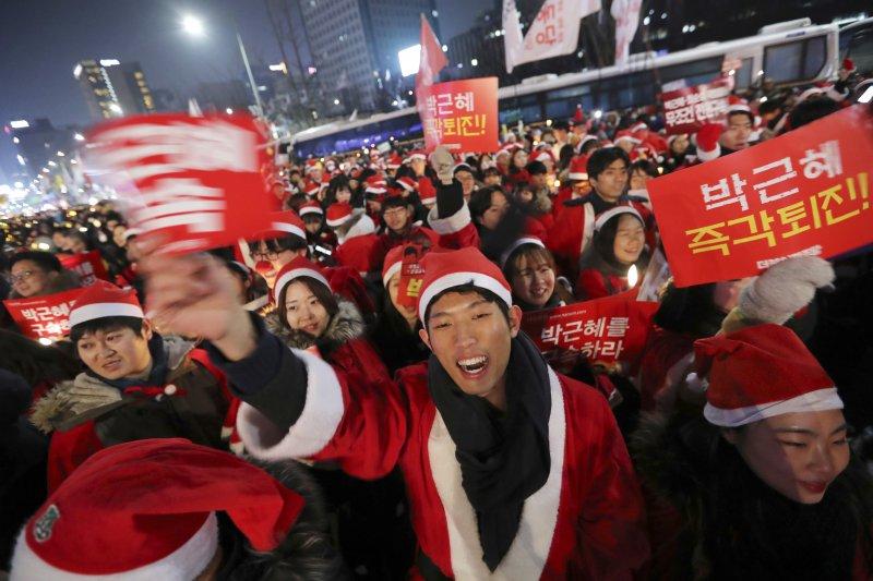 約200-300扮成聖誕老人的年輕人在示威,要求朴槿惠下台。(美聯社)