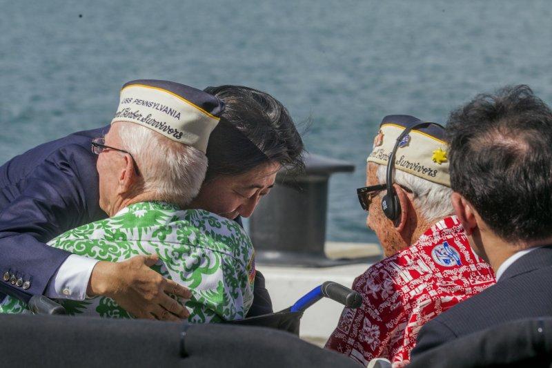 日本首相安倍晉三27日在夏威夷擁抱當年「珍珠港事件」的倖存者。(美聯社)