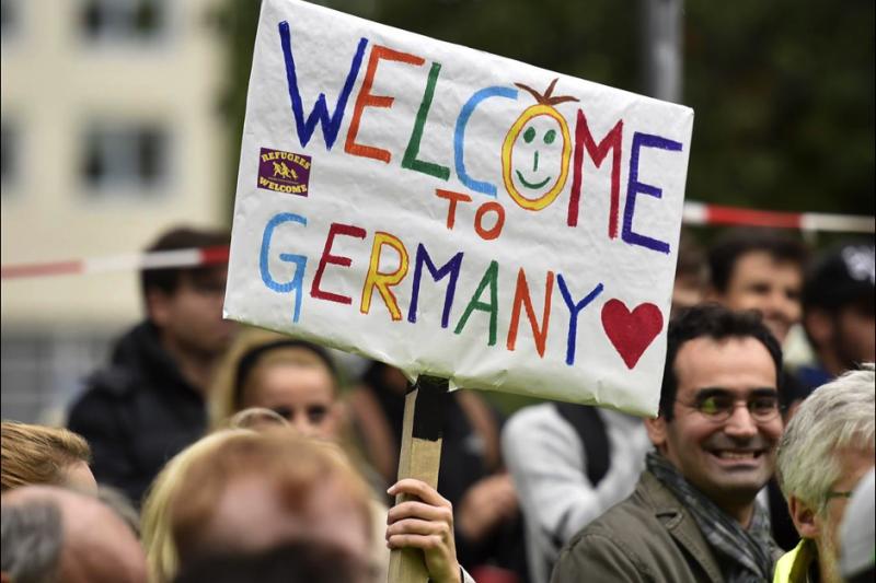 有德國人舉著「歡迎來到德國」的旗幟支持難民。(美聯社)