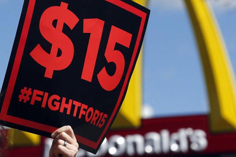 2015年「爭取15美元」(FIGHT FOR 15)的支持者們加入麥當勞抗議者行列,要求政府將基本工資調漲到時薪15美元,2017年部分州的調薪雖然尚未達到勞工的訴求,但少數州已通過法案,指日可待。(AP)