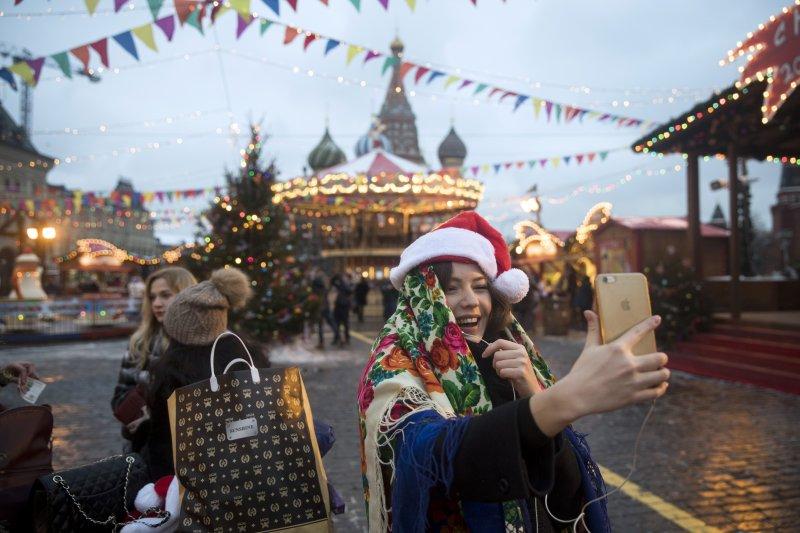 一位俄國女孩在莫斯科紅場的耶誕市集自拍,她的背後就是克里姆林宮。(美聯社)