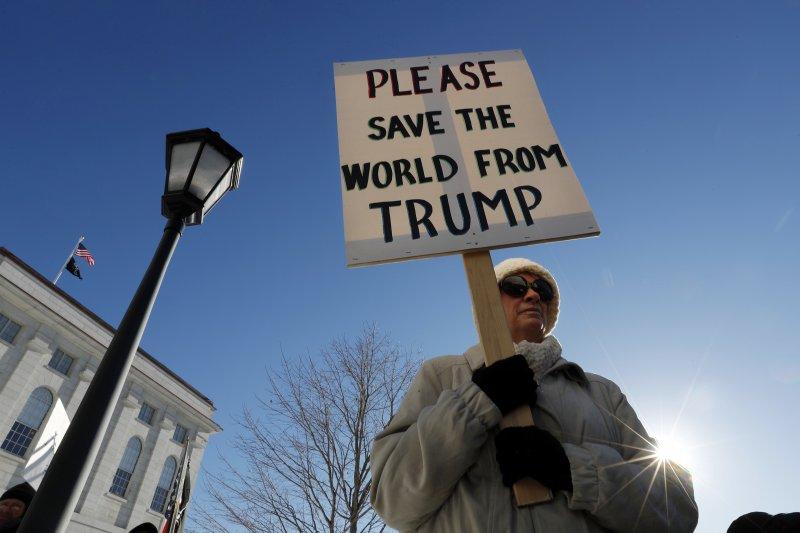 川普抗議者高舉「請從川普手中救救這個世界」標語。(美聯社)