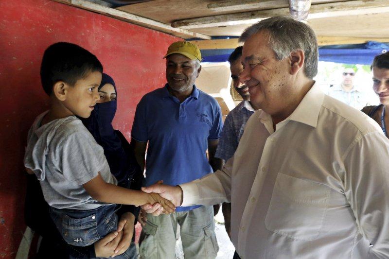聯合國新任秘書長古特雷斯與敘利亞難民兒童握手。(美聯社)
