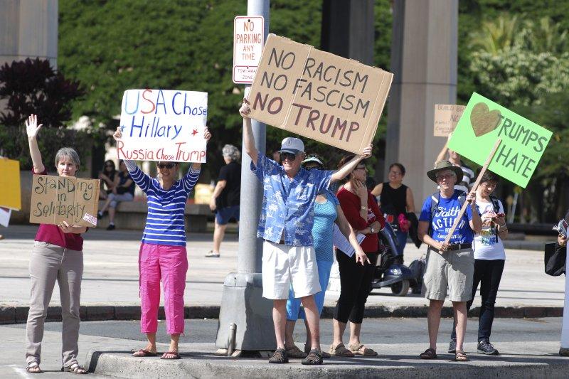 川普當選後民眾聚集在選舉人團會議場地外抗議,高舉「不要種族主義,不要法西斯主義,不要川普」標語。(美聯社)