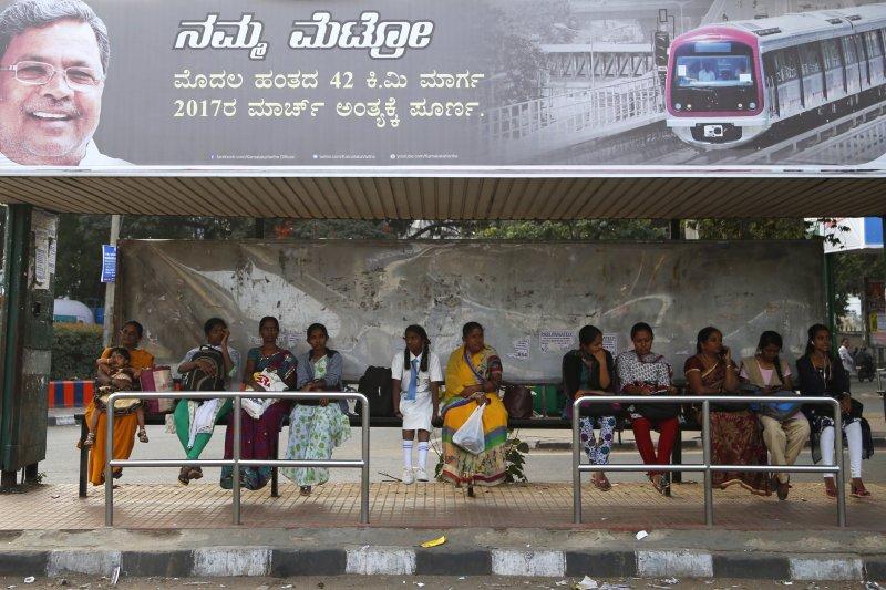 多名印度女性正在邦加羅爾的公車站等車。(美聯社)