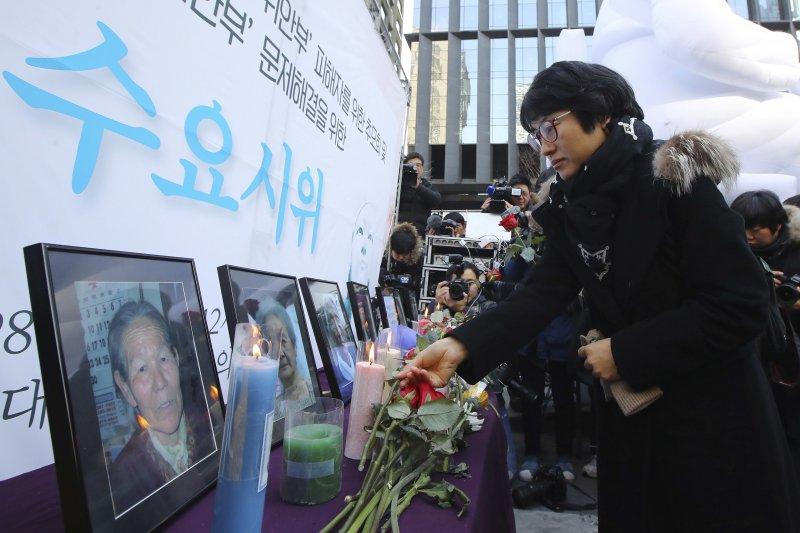 南韓民眾2016年12月在過世慰安婦肖像前致意,抗議日本戰時罪行。(AP)