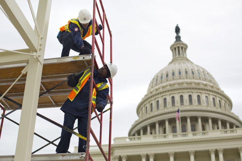 美國新任總統川普的就職典禮1月20日在即,工作人員趕工搭建舞台,但對許多受邀出演的表演人員和民眾來說,他們不知道該不該去。(AP)