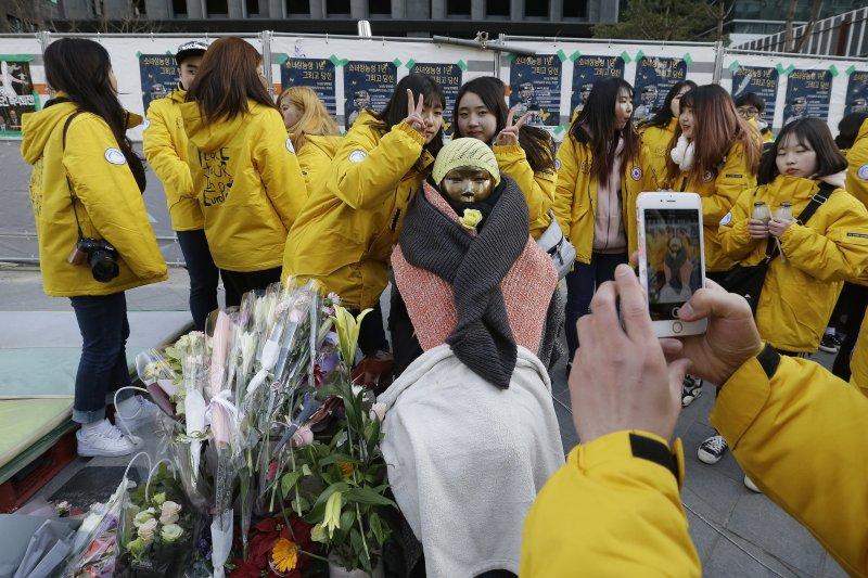 一群南韓女大生在日本駐南韓大使館外的慰安婦少女像旁攝影留念。(美聯社)
