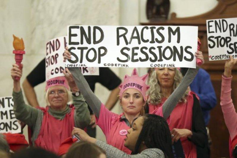美國準司法部長賽辛斯參加聽證會接受質詢時,反對這項人事案的民眾舉牌抗議(AP)