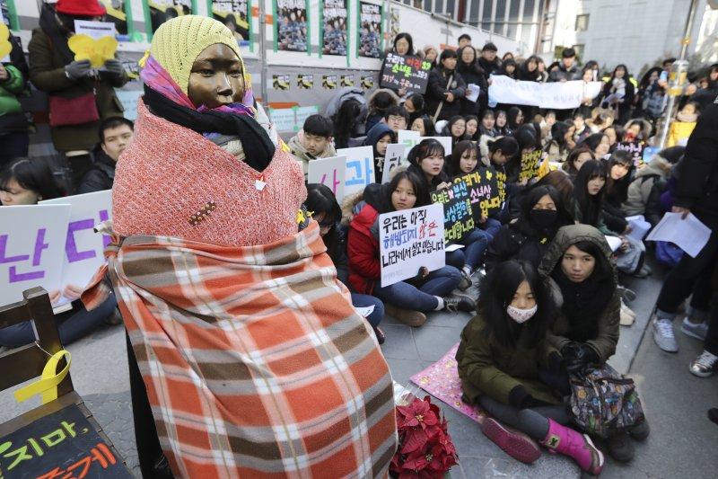 位於首爾的日本大使館外,11日聚集了許多民眾。他們舉著標語在慰安婦少女像旁表示抗議,民眾深怕慰安婦少女像「受寒」,紛紛為她披上了毛帽、毛衣。(美聯社)