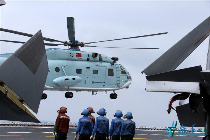 中國海軍遼寧艦,艦面官兵準備回收1架正在著艦的直升機(新華社)