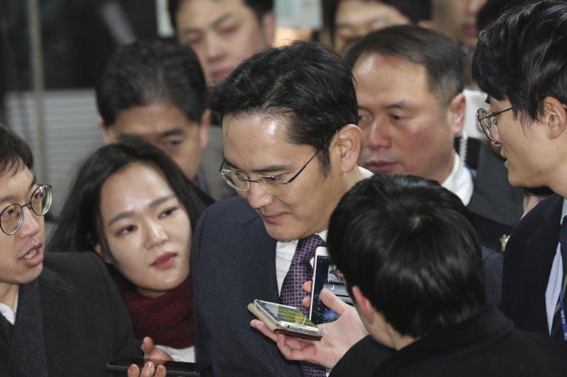 三星副會長李在鎔18日進入首爾法院時,被大批媒體包圍。(美聯社)