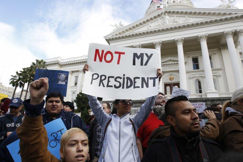 美國加州沙加緬度的民眾20日舉行反川普遊行,抗議者高舉「不是我的總統」海報。(美聯社)