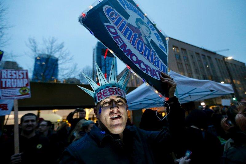 美國西雅圖的民眾20日發動反川普示威,一位抗議者把自己打扮成自由女神的模樣。(美聯社)