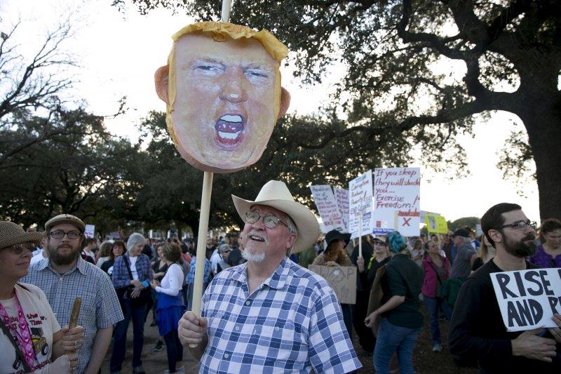 德州奧斯汀的民眾20日發動反川普示威,抗議者高舉川普的頭像遊行。(美聯社)