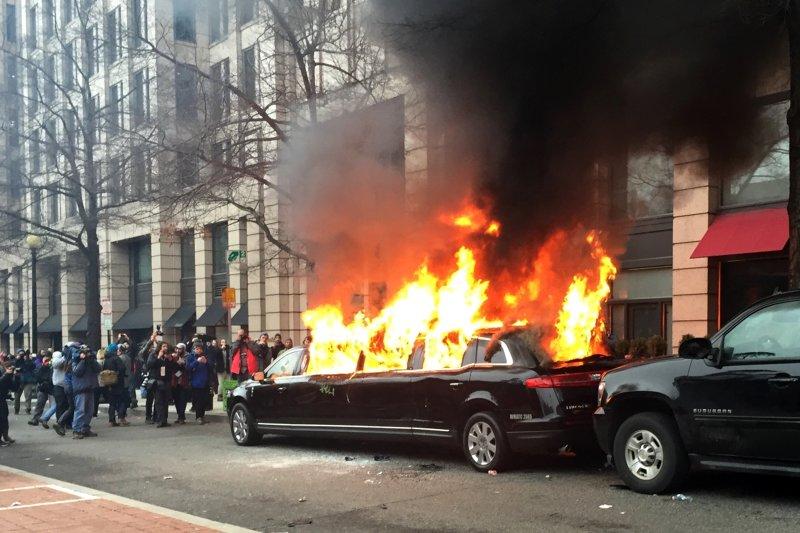 川普就職當天華府出現大批民眾抗議,一輛停在路邊的加長禮車也被人引燃起火。(美聯社)