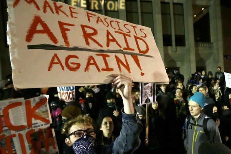華盛頓大學20日出現大批反川普的抗議民眾,其中一人高舉「讓法西斯再次恐懼」的標語。(美聯社)