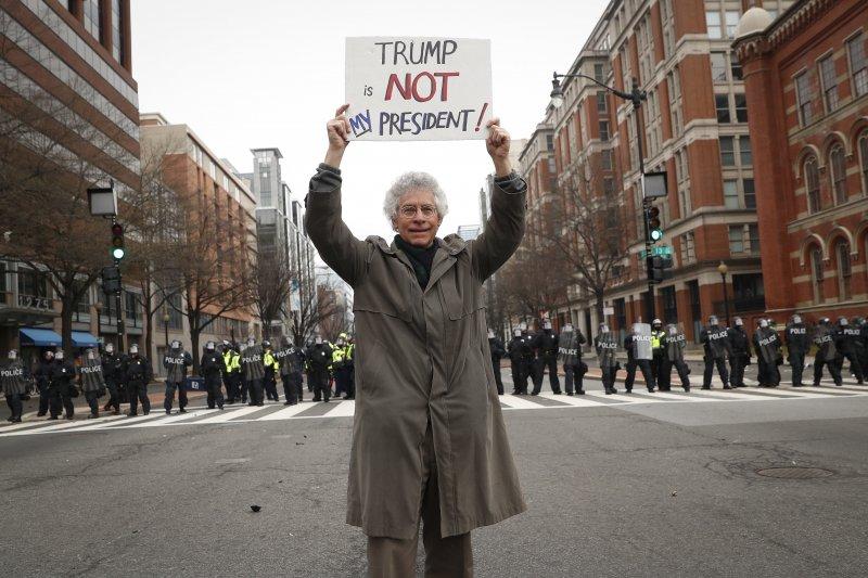 一位民眾在華府街頭高舉抗議紙板:川普不是我的總統!(美聯社)